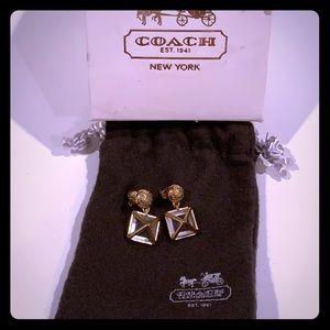 Short dangly gold Coach earrings